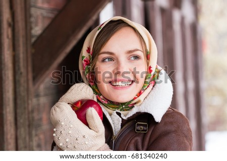 girl in a colorful scarf and with a red apple is standing on the porch of an old wooden house