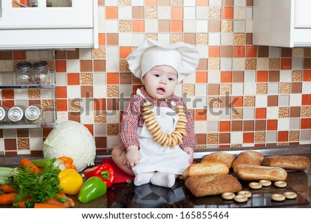 Girl in a cook cap with a ladle in a hand sits on a kitchen table - stock photo
