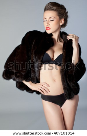 Girl in a dark fur coat and underwear. It stands on a gray background. The model removed the hair in her hair and red lips.