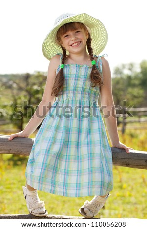 Girl in a dress and hat sitting on the fence