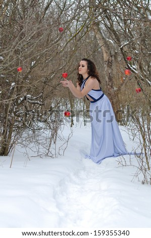 girl in a dress disrupts the apple in the winter  - stock photo