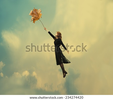 girl in a dress holding a dry leaf and flies on a windy day  - stock photo