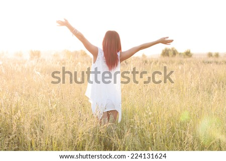 Girl in a dress on a bright sunny field
