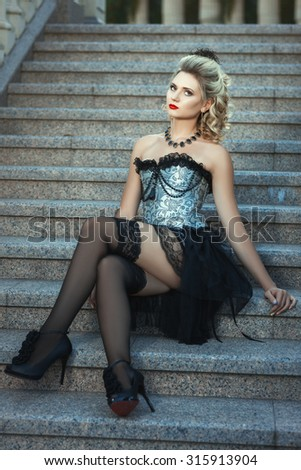 Girl in a dress with a corset and stockings sitting on the stairs. - stock photo