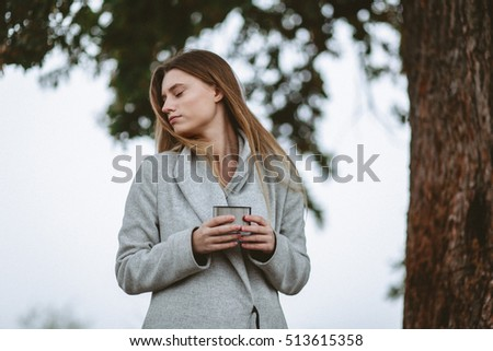 Girl in a field in jacket holding a cup of tea