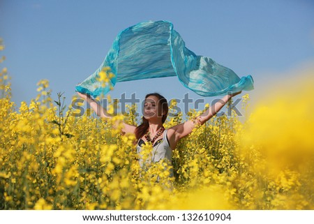 girl in a field of yellow flowers with a blue scarf