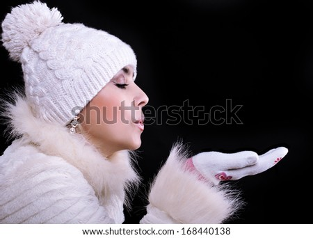 Girl in a fur coat, hat, and gloves on a black background blows away with the palms - stock photo