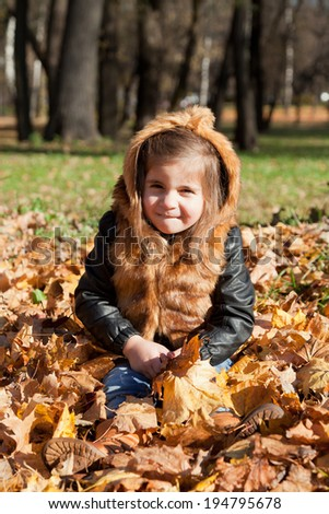 girl in a fur jacket sits on the fallen-down autumn leaves