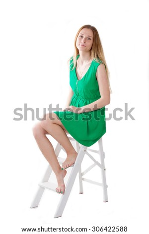 girl in a green dress sitting on a stepladder. isolate - stock photo