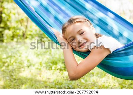 Girl in a hammock enjoys the sunny day - stock photo
