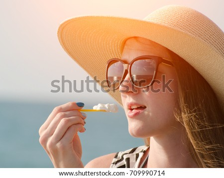 Girl in a hat eating an ice cream spoon. Sea on the background. Sunny day