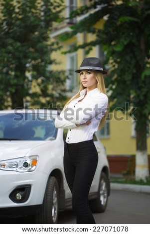 girl in a hat on a background of white car