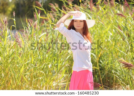 girl in a hat on a background summer landscape - stock photo