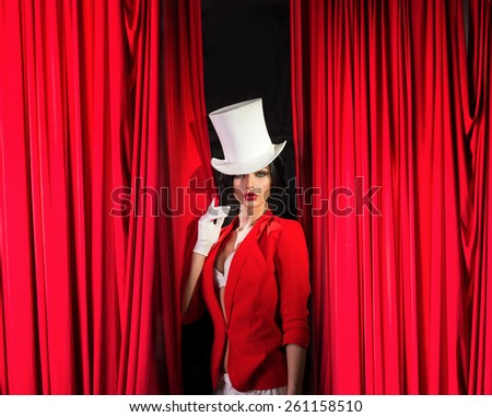 Girl in a jacket and top hat, in the wings of the theater - stock photo