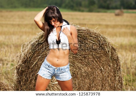 Girl in a jeans shorts on field. - stock photo