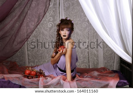 girl in a lilac on a bed of apples