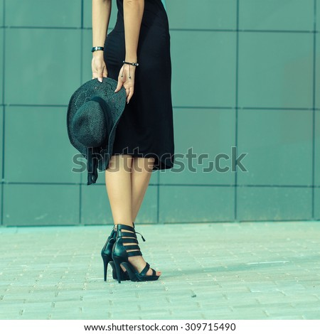 girl in a long dress with a hat and long legs. A close view from the back. - stock photo