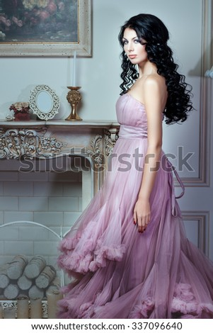 Girl in a magnificent pink dress. She has long black hair and a gentle make-up on her face. - stock photo