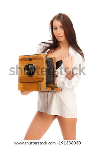 Girl in a man's shirt with a vintage camera on a white background.
