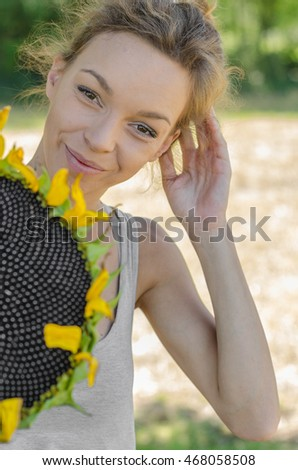 girl in a meadow holding a large sunflower