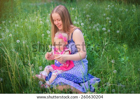 Girl in a pink dress and panama with mother.  Beautiful happy little baby girl sitting with mother on a green meadow with white flowers dandelions on the nature in the park - stock photo