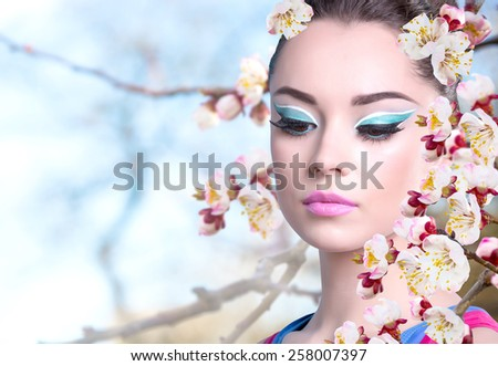 Girl in a pink shirt with spring flowers. Butterfly on a flowering branch of apricot