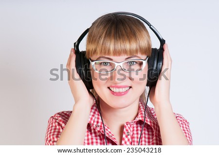 girl in a plaid shirt and glasses  listens to music in earphones - stock photo