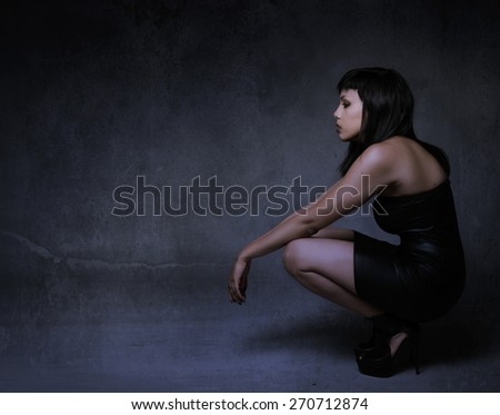 girl in a profile side squatting and looking, nightime - stock photo