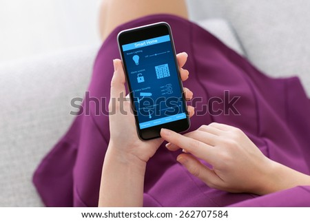 girl in a purple dress holding a phone with program smart home on the screen - stock photo