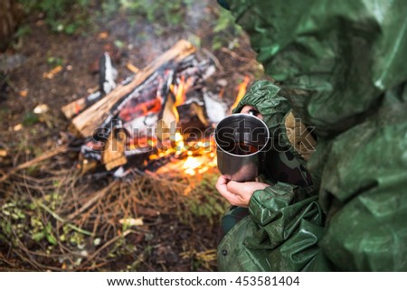 Girl in a raincoat drinking tea from a mug iron. A woman is standing by the fire. Travel, rain forest. - stock photo
