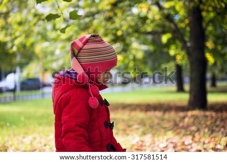 Girl in a red coat walks in autumn park