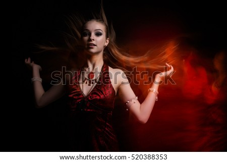 Girl in a red dress. Fire. Black and red portrait.