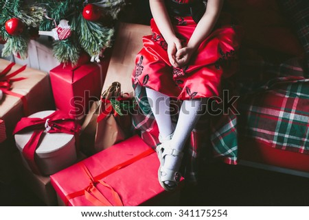 girl in a red dress sitting at the Christmas tree and gifts