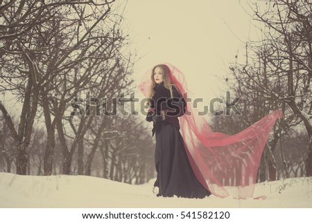 girl in a red veil on the snow in the winter.