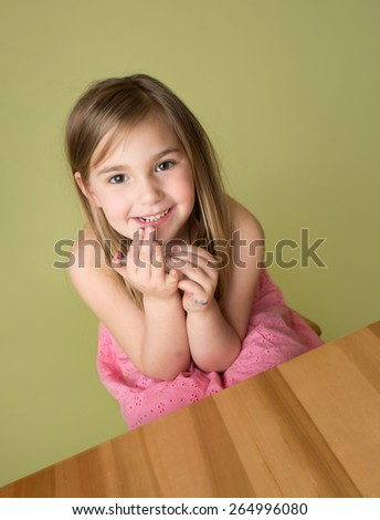 Girl in a school classroom, sitting at desk, smiling and happy - stock photo