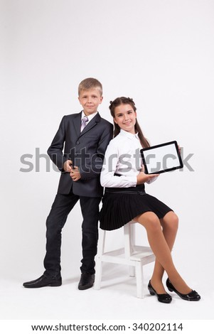 Girl in a skirt and a white blouse sits on a chair on a white background and holds a tablet, standing next to the boy in a business suit. - stock photo