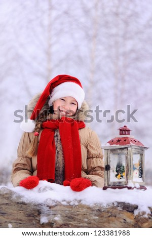 Girl in a snowy forest. Santa's hat on his head. Happy child. - stock photo