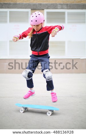 Girl in a sports suit with pink helmet jumping with skateboard