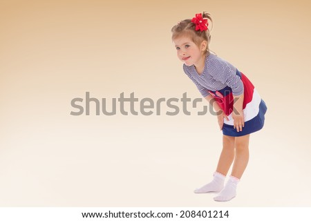 girl in a striped dress holding hands on the knees.kindergarten, the concept of childhood and joy, teens - stock photo