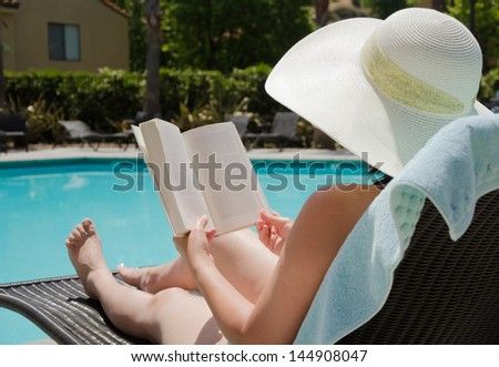 Girl in a summer hat reading a book by the swimming pool