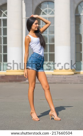 Girl in a t-shirt and shorts in a casual style, in front of a building with columns