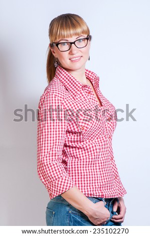 girl in a traditional plaid shirt, stand and holds hands on jeans - stock photo