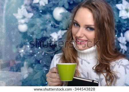 Girl in a warm sweater holding a book and drinking a warm drink