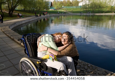 Girl in a wheelchair on a walk around the pond