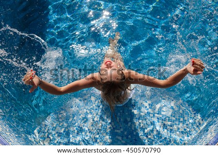 girl in a white bathing suit in the pool splash water