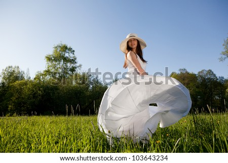 girl in a white dress and hat spinning on a green meadow - stock photo