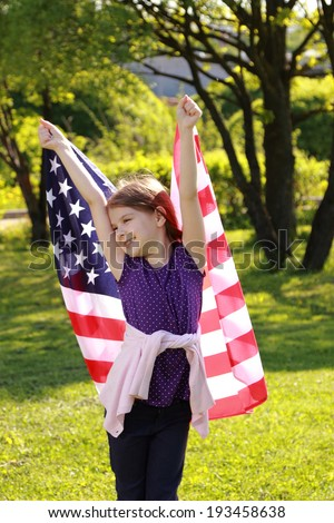 girl in a white dress holding a large American flag in a sunny summer day in the park