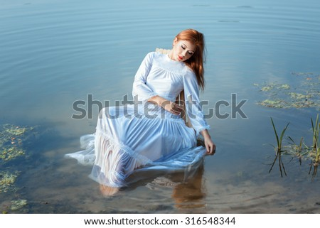 Girl in a white dress sitting on a chair in a lake. Her feet are in the water.
