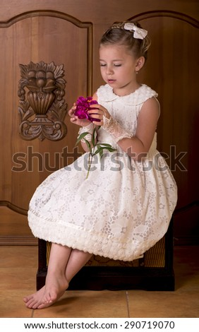girl in a white dress with a flower on a wooden background - stock photo