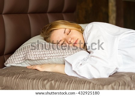girl in a white men's shirt sleeping on the bed - stock photo